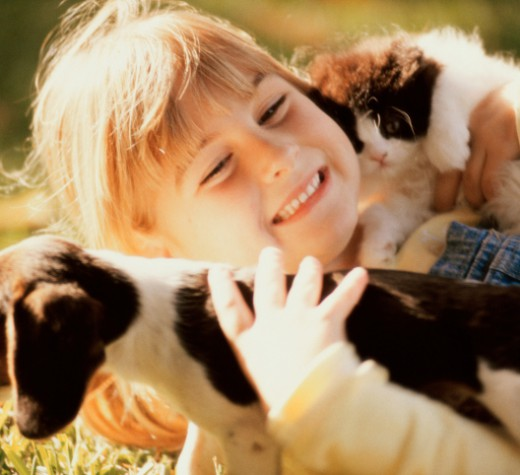Close-up of a girl holding a puppy and a kitten