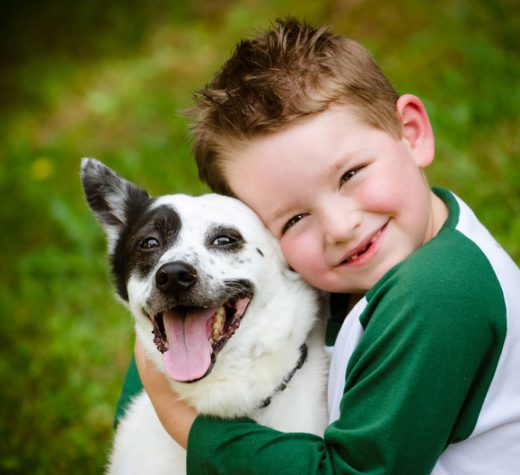 Child lovingly embraces his pet dog, a blue heeler